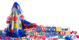 Happy Birthday. Blocks on a white background with copy space, including a party hat and streamers royalty free stock photography