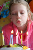 Happy birthday. Young girl blowing candles Royalty Free Stock Photo
