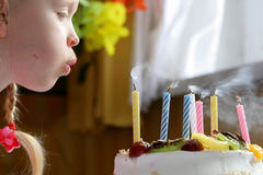 Happy birthday. Little girl blowing birthday candles Stock Photos