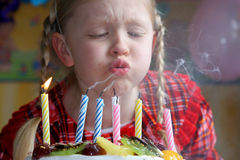Happy birthday. Little girl blowing birthday candles Royalty Free Stock Photo
