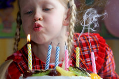Happy birthday. Little girl blowing birthday candles Royalty Free Stock Photos