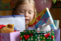 Happy birthday. Little girl looking inside a gift bag Stock Photo