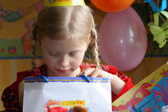 Happy birthday. Little girl looking inside a present bag Stock Images