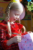 Happy birthday. Little girl looking inside a present bag Royalty Free Stock Photos