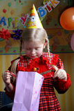 Happy birthday. Little girl looking inside a present bag Stock Photo