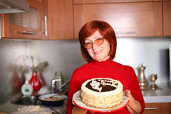 Happy birthday!. A middle aged smiling woman standing in the kitchen holding a cake Royalty Free Stock Image