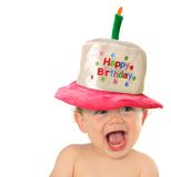 Happy Birthday baby. Smiling baby wearing a Happy Birthday hat royalty free stock images