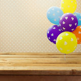Happy birthday background with empty table and balloons. Happy birthday background with empty wooden table and balloons Royalty Free Stock Images