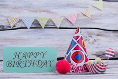Happy Birthday background. Party hat, candies, clowns red nose and card with inscription Happy Birthday royalty free stock image