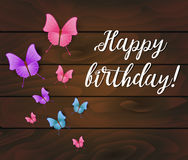 Happy birthday background. Wooden planks with beautiful multicolored butterflies and text message Stock Photography