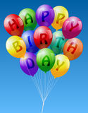 Happy Birthday Balloons. A bunch of colorful realistic looking balloons, lettering Happy Birthday -  on blue sky background Royalty Free Stock Photography