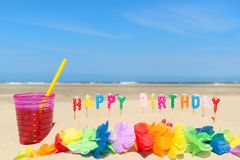 Happy birthday at the beach. Glass lemonade with drinking straw and happy birthday candles at the beach Stock Images