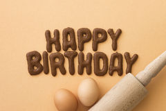 Happy birthday biscuits. Happy Birthday written with Russian bread letter biscuits, eggs and a rolling pin Royalty Free Stock Photos