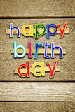 Happy Birthday. Bright multi colored painted letters over brown Royalty Free Stock Image