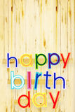 Happy Birthday. Bright multi colored painted letters over woods Royalty Free Stock Images