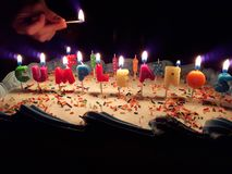 Happy birthday cake with beautiful candles. In the photo you can read `Happy birthday` in spanish stock photo