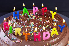 Happy Birthday Cake Candles. Home made chocolate birthday cake topped with Happy Birthday candles Royalty Free Stock Images
