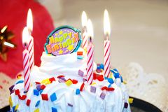 Happy Birthday Cake with Candles. Birthday cake decorated with lit candles and candy sprinkles royalty free stock image