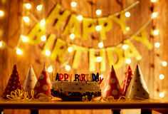Happy birthday cake with candles on the background of garlands a Royalty Free Stock Image