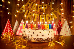 Happy birthday cake with candles on the background of garlands a Royalty Free Stock Photos