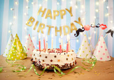 Happy birthday cake with candles on the background of garlands a Stock Photography