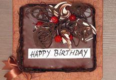 Happy birthday cake. Chocolate cake with candied cherries decoration and happy birthday sign stock photo