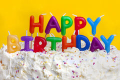 Happy birthday cake with message. Happy birthday cake shot on a yellow background with candles stock images