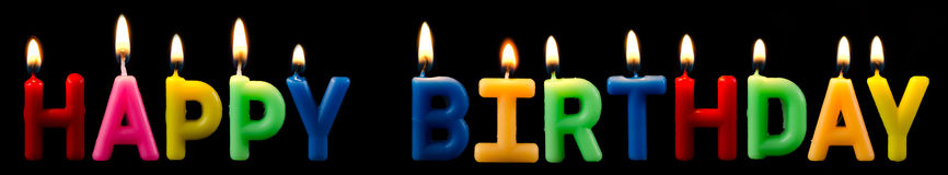 Happy birthday candles. Happy birthday as a logo with candles before black background Royalty Free Stock Photo