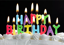 Happy birthday candles on a cake. Colourful happy birthday candles burning on a cake Royalty Free Stock Photography