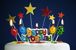 Happy birthday candles on a cake. Happy birthday candles and balloons burning on a cake Royalty Free Stock Photo