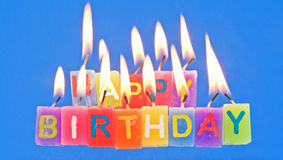 Happy Birthday with candles lighted. An image of the message happy birthday made with lighted candles set on a plain blue background. The flames from the wicks royalty free stock photos