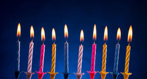 Happy birthday candles over blue. Ten colorful illuminated birthday candles over blue background Royalty Free Stock Photos