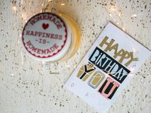 Happy birthday card on a table and Christmas lights. Happy birthday card for anyone on a white background. Christmas lights seemed happy to me, I took them and Stock Image