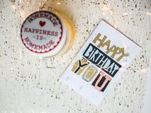 Happy birthday card on a table and Christmas lights. Happy birthday card for anyone on a white background. Christmas lights seemed happy to me, I took them and Stock Photos