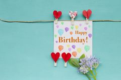 Happy birthday card with red heart clip and purple flower. On blue background royalty free stock image