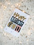 Happy birthday card on a table and Christmas lights. Happy birthday card for anyone on a white background. Christmas lights seemed happy to me, I took them and Royalty Free Stock Images