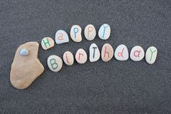 Happy Birthday with carved and painted stone letters over black volcanic sand stock photography