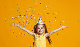 Happy birthday child girl with confetti on yellow background. Happy birthday child girl with confetti on colored yellow background royalty free stock images
