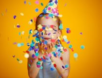 Happy birthday child girl with confetti on yellow background stock image