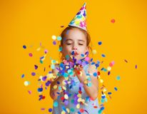 Happy birthday child girl with confetti on yellow background stock photo