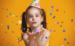 Happy birthday child girl with confetti on yellow background. Happy birthday child girl with confetti on colored yellow background royalty free stock photography