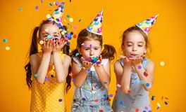 Happy birthday children girls with confetti on yellow background stock photo