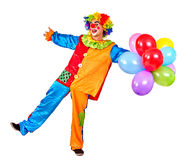 Happy birthday clown holding a bunch of balloons. Royalty Free Stock Photography