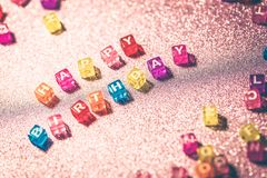 Happy Birthday with colored blocks letters on pink glitter backgrounds. Postcard to celebrate