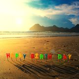 Happy birthday colorful candles on beach sunrise.