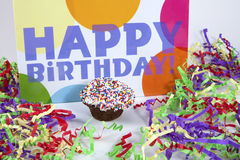 Happy Birthday with Cupcake. Happy Birthday sign and streamers with a decorated cupcake Stock Photo