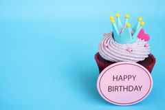 Happy birthday cupcake with crown and pink heart over blue backg Royalty Free Stock Photos