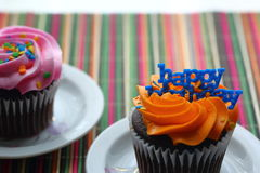 Happy birthday cupcake in orange. Orange cupcake with blue happy birthday writing with a pink cupcake in the background Royalty Free Stock Photos
