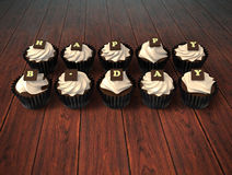Happy Birthday cupcakes on dark wooden background. Happy Birthday cupcakes - illustration of muffins witch beige cream and chocolate white letters on dark brown Stock Photo