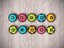 Happy Birthday cupcakes isolated on wood floor background. Happy Birthday cupcakes - top view render illustration of colourful muffins with cream and chocolate Royalty Free Stock Photos